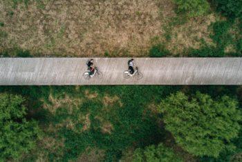 Rzut z lotu ptaka obszaru pokrytego roślinnością, drewniana kładka na środku, a na niej dwóch mężczyzn na rowerach w pozycji leżącej.