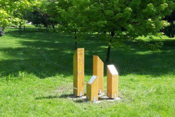 Drewniane słupy z tablicami informacyjnymi na na ścieżce edukacyjnej na tle zieleni.