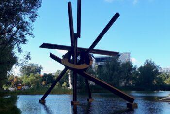 Instalacja na wodzie - Berlin. W tle roślinność trawiasta, drzewiasta i fragmenty zabudowań.