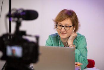 Kobieta siedząca przy laptopie podczas nagrania rozmowy kamerą.
