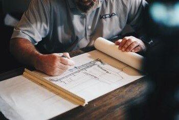 Mężczyzna siedzący przy biurku i projektujący plan budynku.