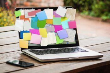 Komputer laptop z karteczkami przyklejonymi na ekranie