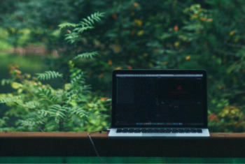 Otwarty laptop stojący na stole przed dużym oknem. W tle widoczny las.