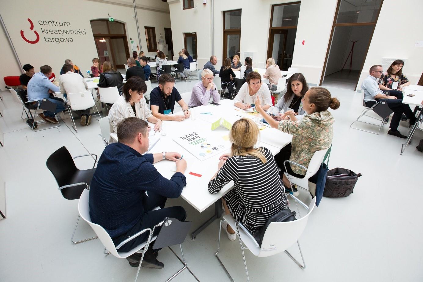 Uczestnicy konferencji przy stołach pracujący wgrupach.