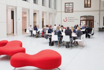 Uczestnicy konferencji na sali warsztatowej przy stołach.